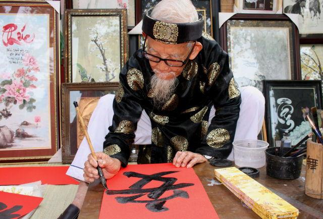 Một ông đồ đang vẽ thư pháp